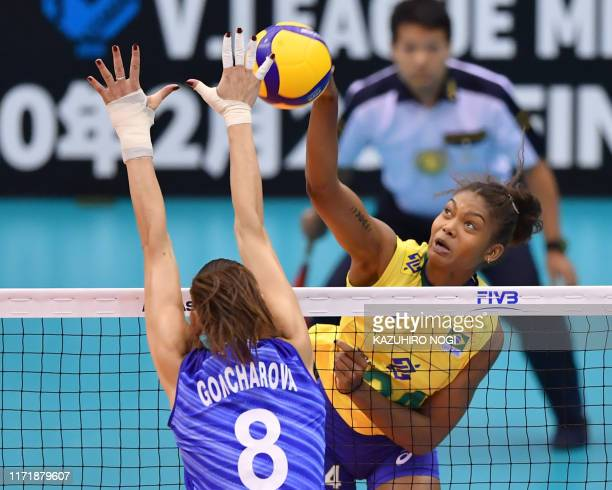 Brazil's Lorene Teixeira spikes the ball over Russia's Nataliya Goncharova during the FIVB Women's World Cup volleyball match between Russia and...