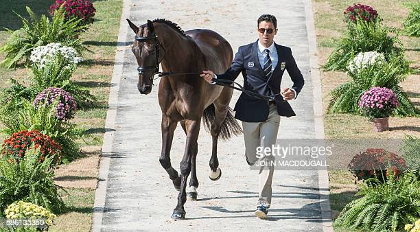 Brazil's Marcio Carvalho Jorge leads Lissy Mac Wayer to a trot during the first horse inspection of the Equestrian's Eventing phase during the 2016...