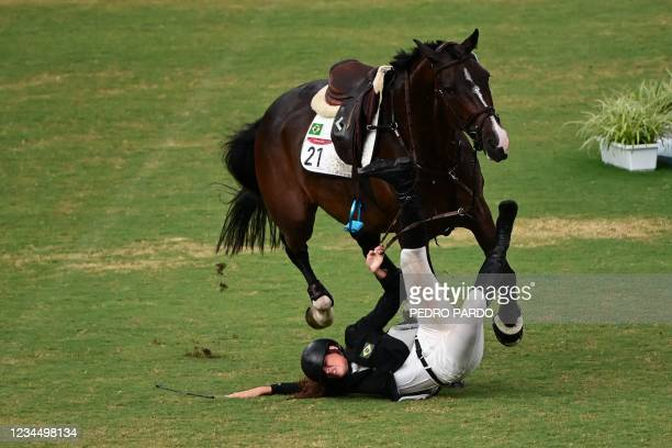 Brazil's Maria Ieda Chaves Guimaraes falls as she competes in the women's individual riding show jumping modern pentathlon during the Tokyo 2020...