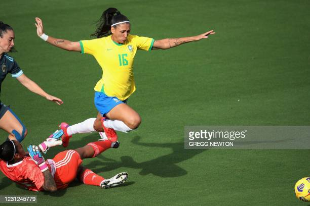 Brazil's midfielder Beatriz evades goal keeper Solana Pereyra and defender Agustina Barroso of Argentina during their SheBelieves Cup international...