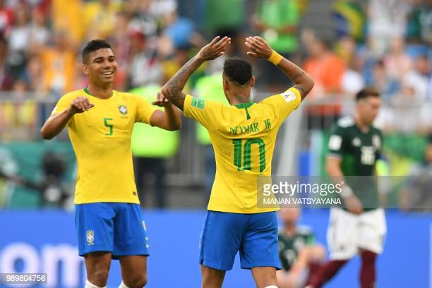 Brazil's midfielder Casemiro and Brazil's forward Neymar celebrate after winning at the end of the Russia 2018 World Cup round of 16 football match...