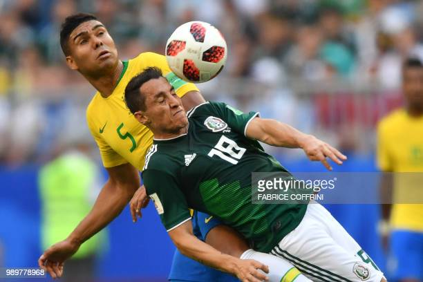 TOPSHOT Brazil's midfielder Casemiro and Mexico's midfielder Andres Guardado vie for the ball during the Russia 2018 World Cup round of 16 football...
