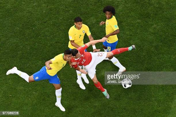 TOPSHOT Brazil's midfielder Casemiro fights for the ball with Switzerland's defender Fabian Schaer during the Russia 2018 World Cup Group E football...