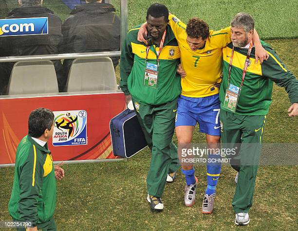 Brazil's midfielder Elano is escorted off the pitch by medics after he was injured during the 2010 World Cup group G first round football match...
