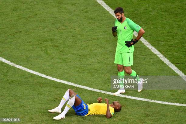 Brazil's midfielder Fernandinho lies on the field as Brazil's goalkeeper Alisson walks past him at the end of the Russia 2018 World Cup quarterfinal...