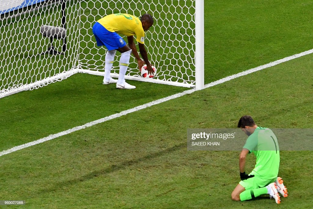 Brazil's midfielder Fernandinho (L) picks up the ball as Brazil's goalkeeper Alisson reacts after conceding the second goal during the Russia 2018 World Cup quarter-final football match between Brazil and Belgium at the Kazan Arena in Kazan on July 6, 2018. (Photo by SAEED KHAN / AFP) / RESTRICTED