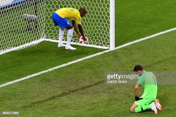 Brazil's midfielder Fernandinho picks up the ball as Brazil's goalkeeper Alisson reacts after conceding the second goal during the Russia 2018 World...