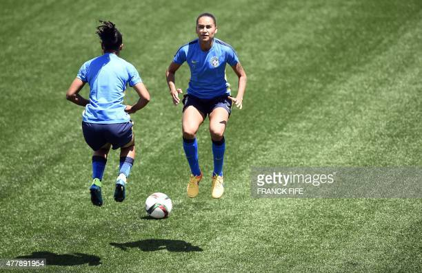 Brazil's midfielder Gabriela jumps with a teammates during a training session at the Moncton Stadium New Brunswick on June 20 2015 on the eve of...