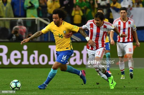 Brazil's midfielder Marcelo vies for the ball with Paraguay's midfielder Oscar Romero during their 2018 FIFA World Cup qualifier football match in...