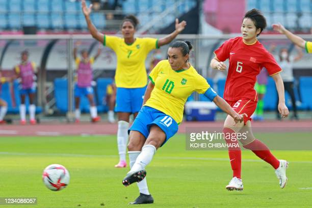 Brazil's midfielder Marta shoots to score the opening goal during the Tokyo 2020 Olympic Games women's group F first round football match between...