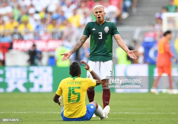 Brazil's midfielder Paulinho argues with Mexico's defender Carlos Salcedo during the Russia 2018 World Cup round of 16 football match between Brazil...