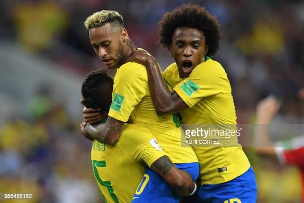 TOPSHOT Brazil's midfielder Paulinho celebrates with Brazil's forward Neymar and Brazil's forward Willian after scoring Brazil's opening goal during...