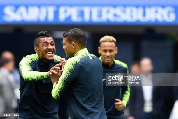 Brazil's midfielder Paulinho jokes with Brazil's defender Thiago Silva as Brazil's forward Neymar looks at them during a training session at the...