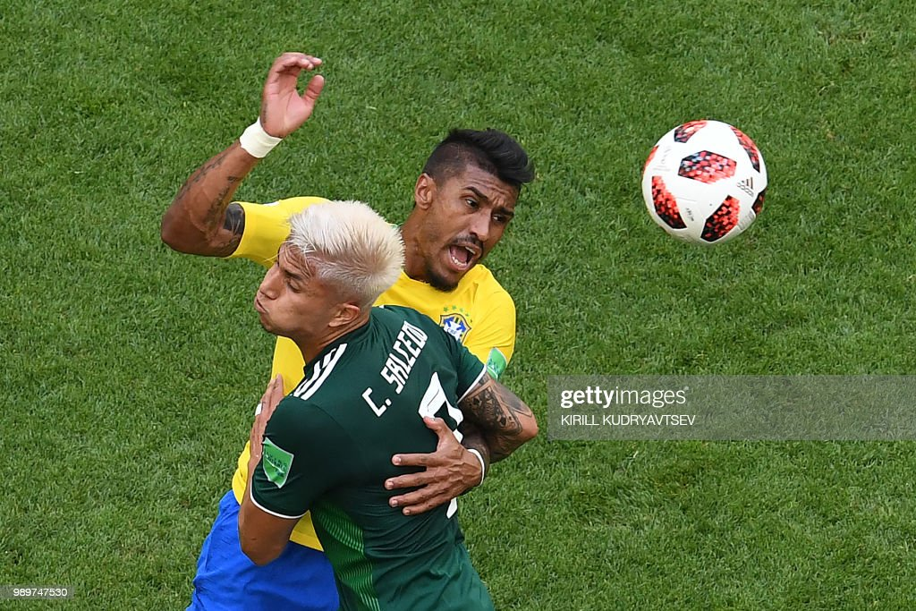 Brazil's midfielder Paulinho (R) vies with Mexico's defender Carlos Salcedo during the Russia 2018 World Cup round of 16 football match between Brazil and Mexico at the Samara Arena in Samara on July 2, 2018. (Photo by Kirill KUDRYAVTSEV / AFP) / RESTRICTED