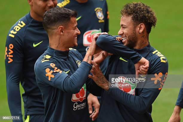 Brazil's midfielder Philippe Coutinho and Brazil's striker Neymar share a joke as they take part in a training session at Anfield stadium in...