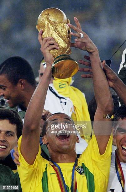 Brazil's midfielder Rivaldo hoists the World Cup trophy as the whole Brazilian team cheers after winning 20 against Germany in match 64 of the 2002...