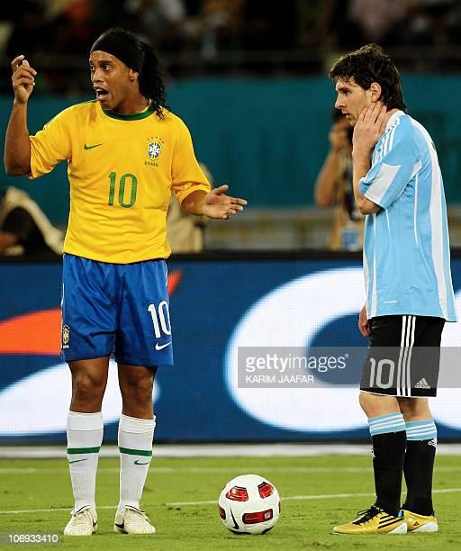 Brazil's midfielder Ronaldinho gestures next to Argentina's striker Lionel Messi during their friendly football match at Khalifa Stadium in Doha on...