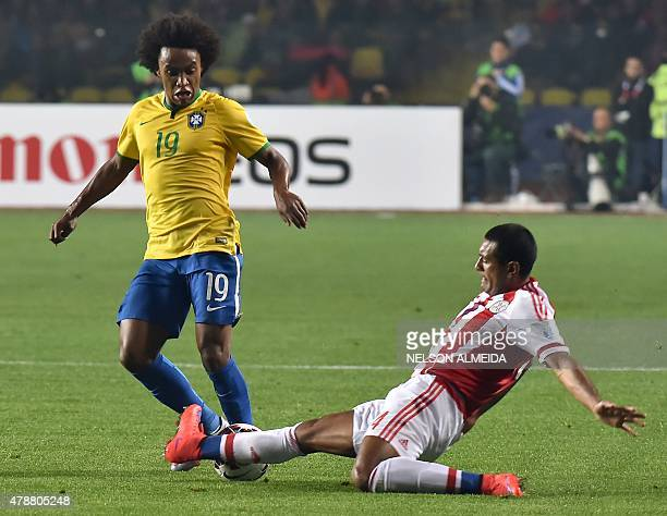 Brazil's midfielder Willian vies for the ball with Paraguay's defender Paulo Da Silva during their 2015 Copa America football championship...