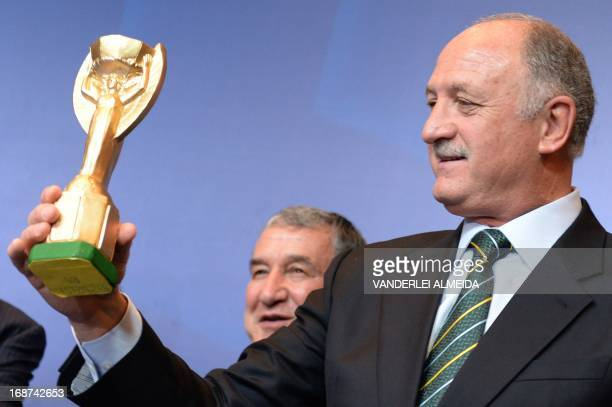 Brazil's national football team coach Luiz Felipe Scolari holds a replica of the FIFA World Cup Jules Rimet trophy during a press conference at a...