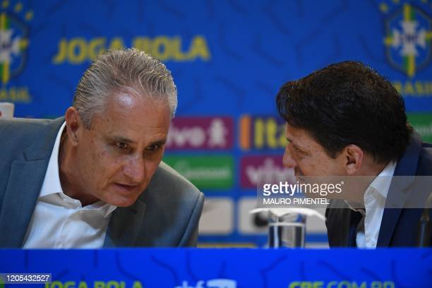 Brazil's national football team coach Tite listens to team director Juninho Paulista during a press conference to announce the list of players for...