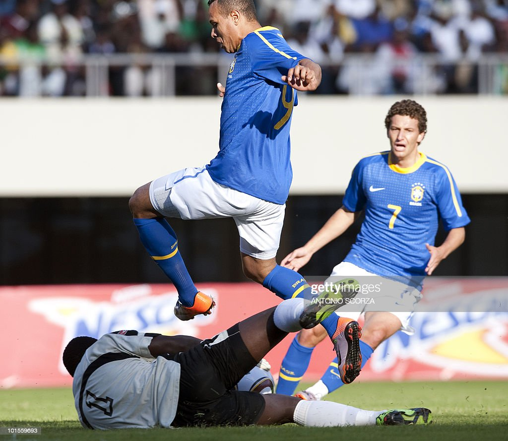 Brazil's national football team forward Luis Fabiano (c) jumps over Zimbabwean goalkeeper Edmore Sibanda (L) as Brazil's Elano looks on at the National Sport Stadium in Harare on June 2, 2010 during a friendly football match. The Brazilian national team is preparing for the 2010 FIFA World Cup in South Africa.
