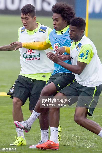 Brazil's national football team players Willian Geferson and Roberto Firmino vie for the ball during a training session on June 2 2015 at the Granja...