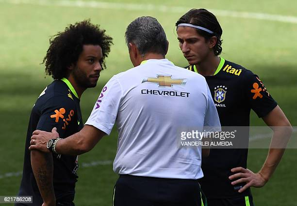 Brazil's national team coach Tite speaks with players Marcelo and Filipe Luis during a training session at Mineirao stadium in Belo Horizonte Minas...