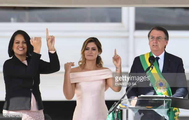 Brazil's new President Jair Bolsonaro addresses the crowd as First Lady Michelle Bolsonaro and an interpreter interpret the speech in sign language...