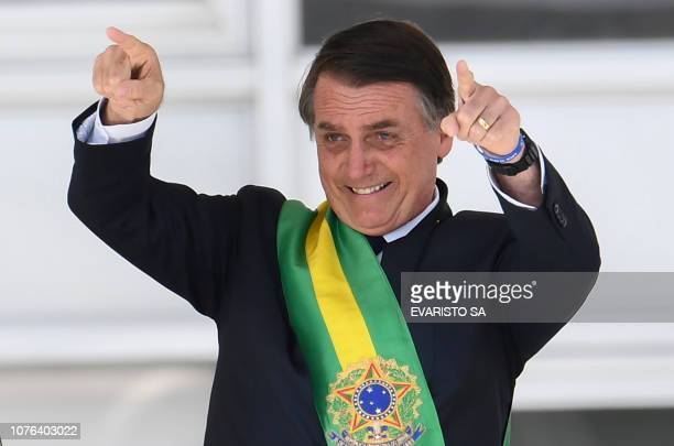 Brazil's new president Jair Bolsonaro gestures after receiveing the presidential sash from outgoing Brazilian president Michel Temer at Planalto...
