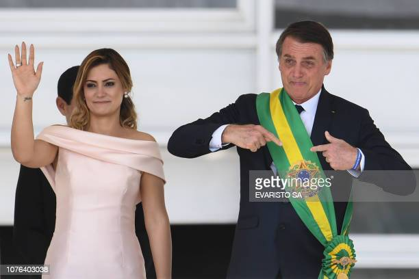 Brazil's new president Jair Bolsonaro gstures next to his wife Michelle Bolsonaro after receiveing the presidential sash from outgoing Brazilian...