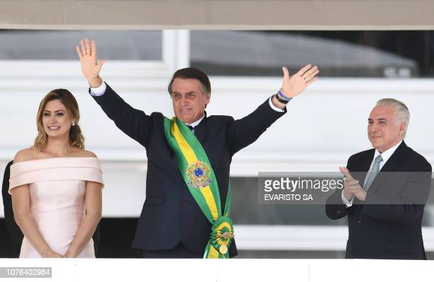 Brazil's new president Jair Bolsonaro waves to supporters next to his wife Michelle Bolsonaro after receiveing the presidential sash from outgoing...
