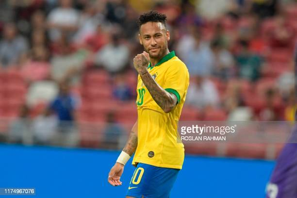 Brazil's Neymar celebrates during the friendly international football match between Brazil and Senegal at the National Stadium in Singapore on...