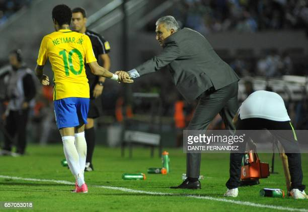 Brazil's Neymar celebrates his goal with coach Tite during their 2018 FIFA World Cup qualifier football match against Uruguay at the Centenario...