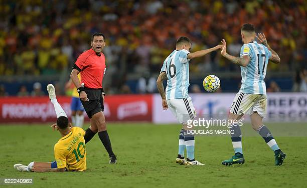 Brazil's Neymar falls next to Chilean referee Julio Bascunan as Argentina's Angel Correa and Nicolas Otamendi during the 2018 FIFA World Cup...