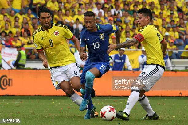 TOPSHOT Brazil's Neymar is marked by Colombia's Abel Aguilar and James Rodriguez during their 2018 World Cup qualifier football match in Barranquilla...
