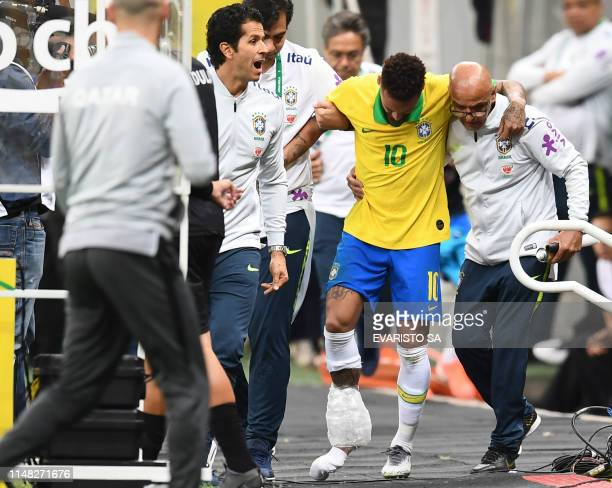 TOPSHOT Brazil's Neymar leaves the pitch injured during a friendly football match against Qatar at the Mane Garrincha stadium in Brasilia on June 5...