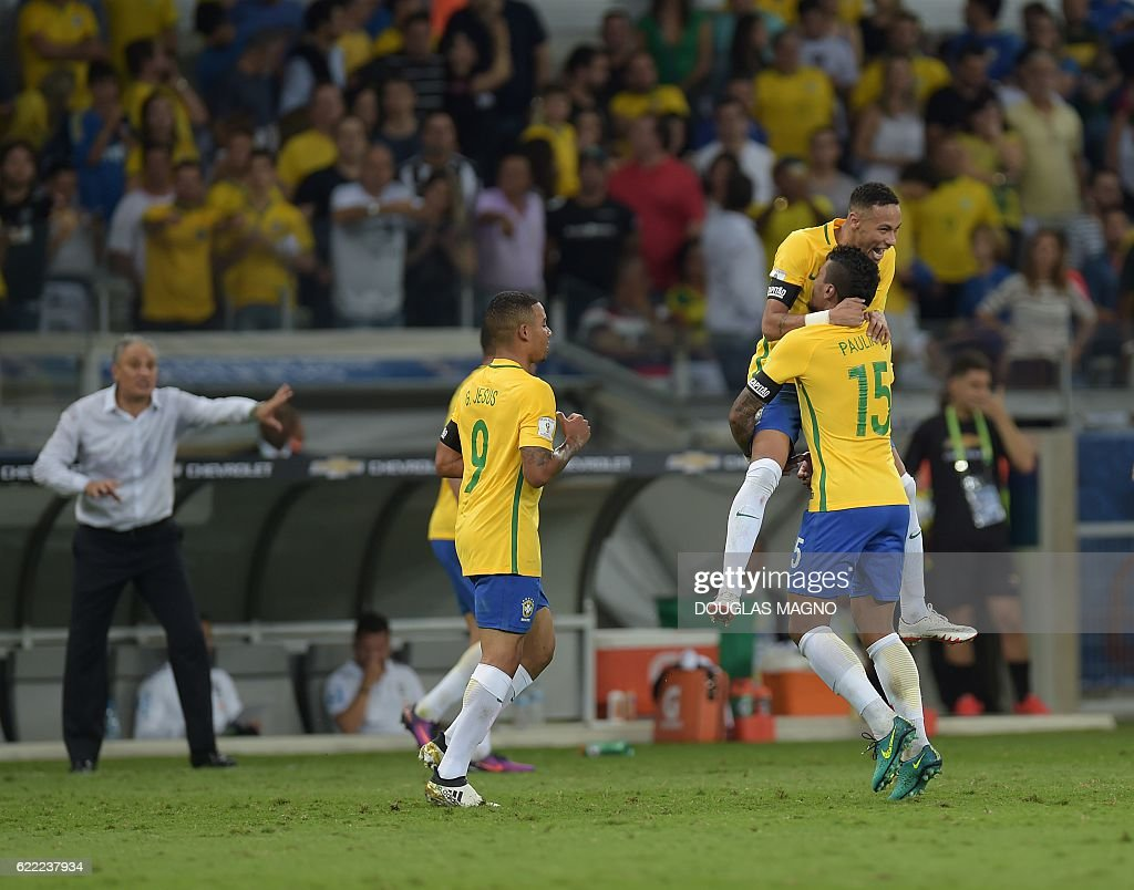 Brazil's Neymar (top), Paulinho (R) and Gabriel Jesus celebrate during their 2018 FIFA World Cup qualifier football match in Belo Horizonte, Brazil, on November 10, 2016. / AFP / DOUGLAS
