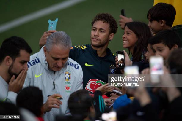 Brazil's Neymar poses for a selfie with a fan as coach Tite signs autographs to supporters after a training session of the national football team...