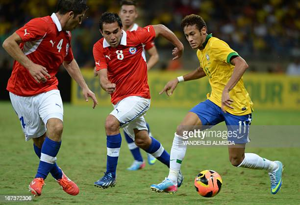 Brazil's Neymar vies for the ball with Cristian Alvarez and Fenando Meneses of Chile during their friendly football match at the Mineirao stadium in...