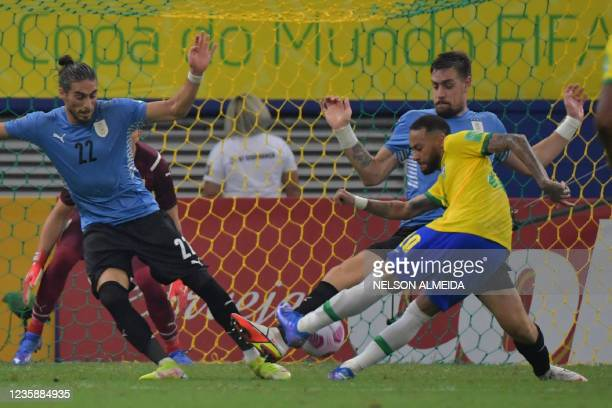 Brazil's Neymar vies for the ball with Uruguay's Martin Caceres and Uruguay's Sebastian Coates during their South American qualification football...