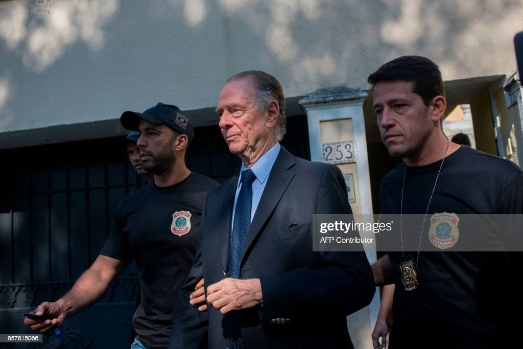 Brazil's Olympic Committee chief Carlos Nuzman (C) is escorted from his home by federal police in Rio de Janeiro on October 5, 2017. Brazilian police on October 5 arrested the chairman of the Brazilian Olympic Committee as part of a probe into alleged buying of votes to secure Rio's hosting of the 2016 Games. / AFP PHOTO / Mauro PIMENTEL