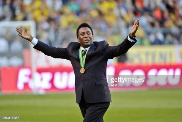 Brazil's 'Pele' aka Edison Arantes do Nascimento acknowledges cheers from the audience as he enters Rasunda stadium in Stockholm on August 15 prior...