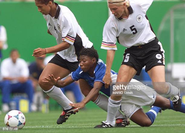 Brazil's Pethina is tripped up by Stephanie Ann Jones and Doris Fitschen of Germany in the first half of their 1999 FIFA Women's World Cup match at...