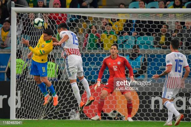 Brazil's Philippe Coutinho and Paraguay's Gustavo Gomez jump for the ball as Paraguay's goalkeeper Roberto Fernandez loosk on during their Copa...