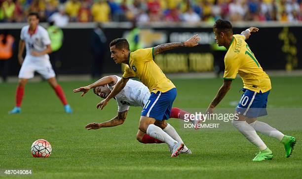 Brazil's Philippe Coutinho makes his way toward the goal past Costa Rica's Christian Gamboa and in front of Brazil's Neymar during the friendly match...