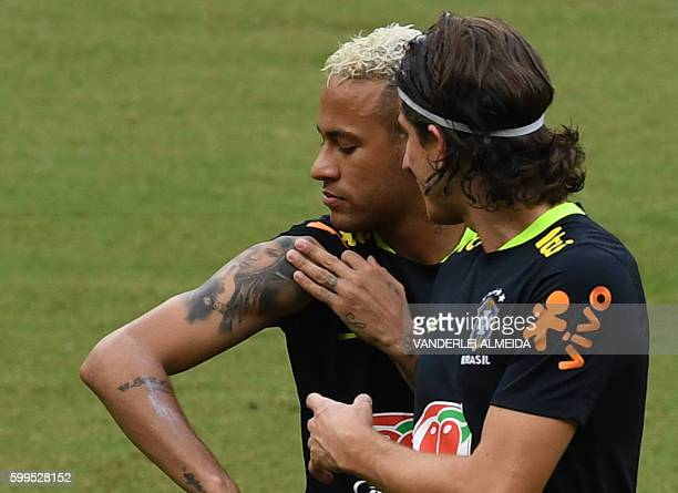 Brazil's player Neymar shows his tattoo to teammate Filipe Luis during a training session on September 5 2016 at the Arena Amazonia stadium in Manaus...
