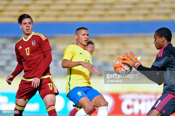 Brazil's player Richarlison vies for the ball with Venezuela's player Josue Mejias and goalkeeper Wuilker Farinez during their South American...