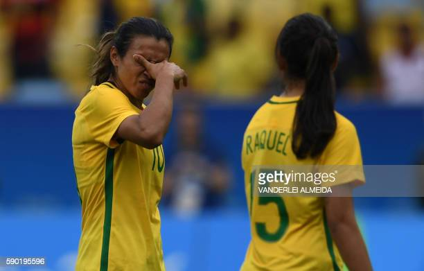 TOPSHOT Brazil's players Marta and Raquel Fernandes leave in dejection after losing in their Rio 2016 Olympic Games Women's semifinal football match...