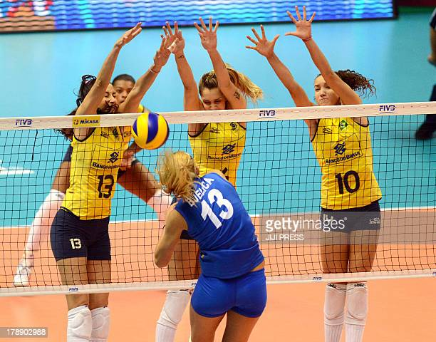 Brazil's players Sheilla Castro Thaisa Menezes and Gabriela Braga Guimaraes block the ball spiked by Ana Bjelica of Serbia during the women's...