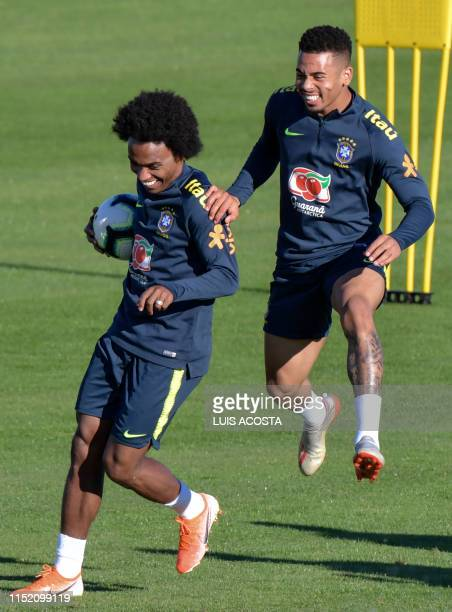 Brazil's players William and Gabriel Jesus laugh during a practice session in Porto Alegre, Brazil, on June 26 on the eve of the Copa America quarter...